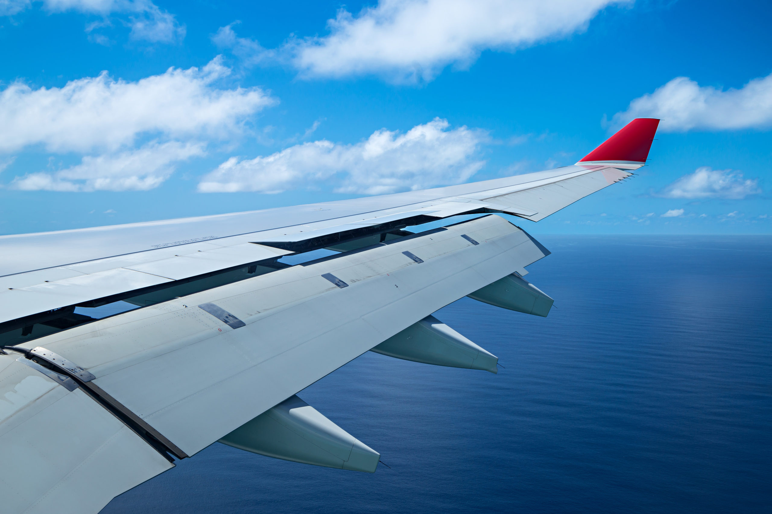 wing of an airplane aero plane with landing flaps on blue cloudy sky